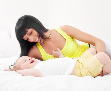 happy young mother and her baby on the bed at home Stock Photo - 8860590