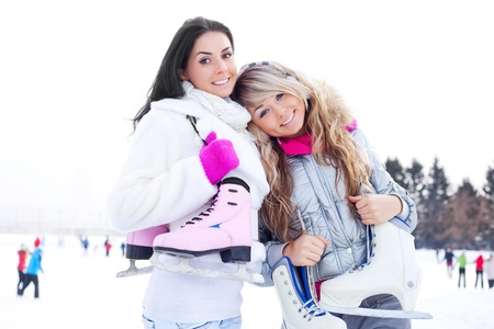 skating rink: two beautiful girls wearing warm winter clothes ice skating