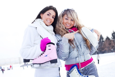 iceskating: two beautiful girls wearing warm winter clothes ice skating