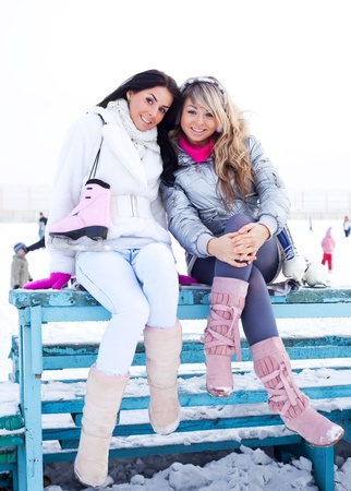 two beautiful girls wearing warm winter clothes ice skating photo