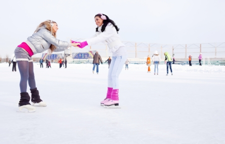 rink: two beautiful girls ice skating outdoor on a warm winter day
