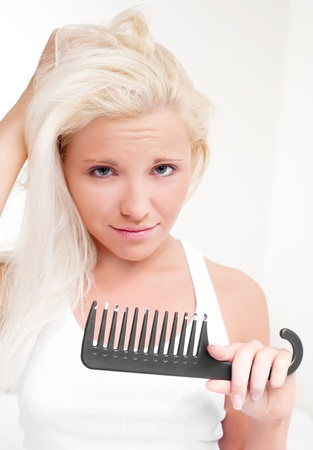 beautiful young blond woman having problems with hair photo