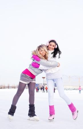 patinando: dos chicas guapas patinaje al aire libre en un d�a c�lido invierno