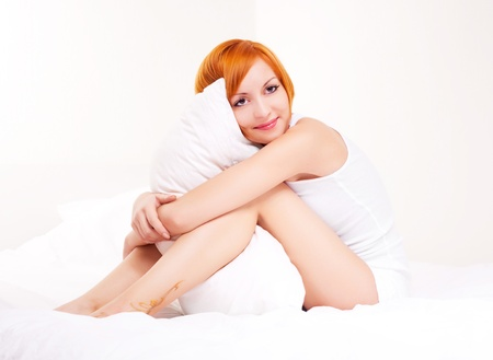 beautiful young ginger woman with a pillow on the bed at home photo