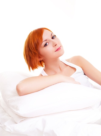 beautiful young ginger woman with pillows on the bed at home photo