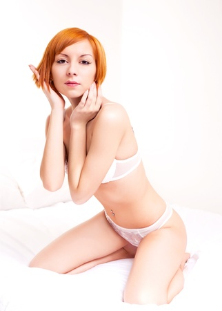 sexy young ginger woman wearing underwear on the bed at home photo