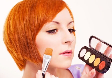 beautiful young woman applying rouge on her face  Stock Photo - 8942489