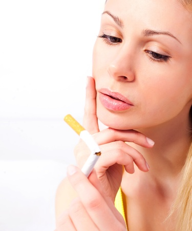 anti tobacco: young woman breaking a cigarette and frowning, isolated against white background