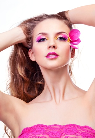 beautiful young woman with creative makeup with tulip petals and long curly hair photo