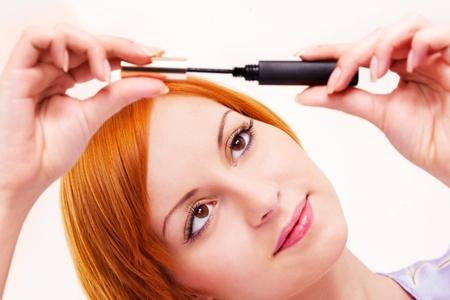 visagiste: beautiful young woman applying mascara on her eyelashes