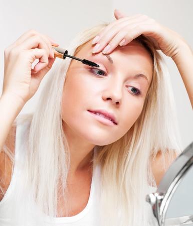 verdunkeln: Beautiful young Woman applying Mascara auf ihre Wimpern Lizenzfreie Bilder