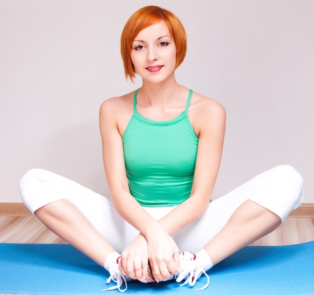 ankles sexy: beautiful young sporty woman stretching the muscles of her legs on the mat at home Stock Photo