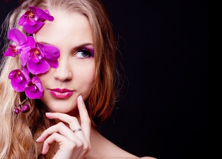 appealing attractive: beautiful young woman with long curly hair and an orchid