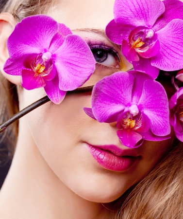 portrait of a beautiful young blond woman with an orchid photo