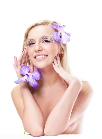 beautiful young blond woman with unusual makeup with feathers and orchids photo
