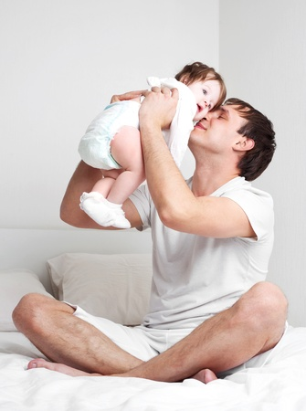young father with his six months old daughter on the bed at home  Stock Photo - 9155455