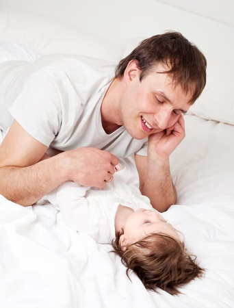 young father with his six months old daughter on the bed at home (focus on the man) Stock Photo - 9155457