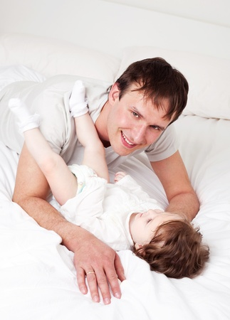 young father with his six months old daughter on the bed at home (focus on the man) Stock Photo - 9155451