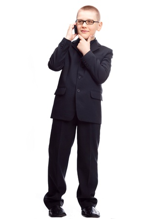 ten year old blond boy wearing a costume talking on the cellphone, isolated against white Stock Photo - 9294862