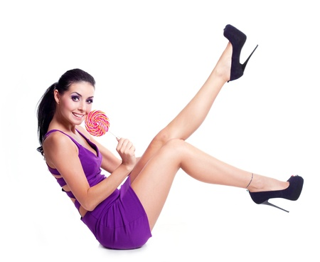 pretty smiling brunette woman with a lollipop in her hand photo
