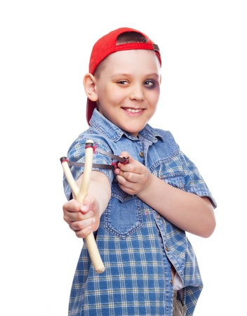 naughty boy with a bruise under his eye holding a slingshot and aiming at something photo