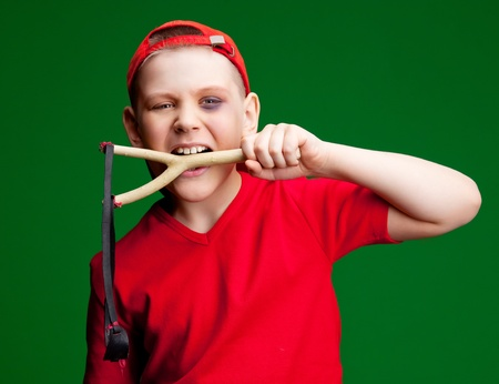 naughty boy with a bruise under his eye holding a slingshot   photo