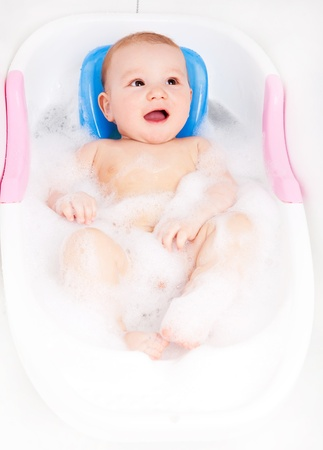 baby on chair: cute six months old baby sitting in the baby bath chair   Stock Photo