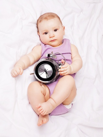 up wake: cute six months old baby on the bed with an alarm clock