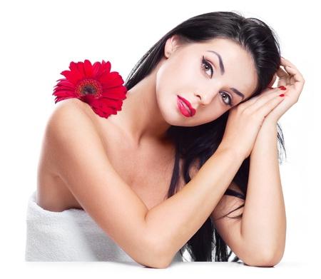 unas largas: sexy joven morena con una flor roja, aislado contra blanco