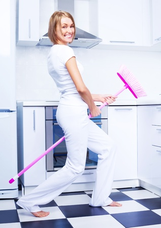 beautiful young housewife with a broom in the kitchen photo