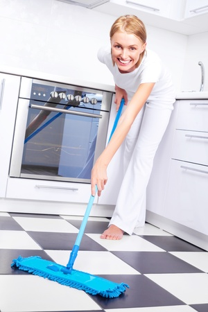 beautiful young housewife with a mop in the kitchen photo