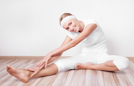 hamstring: beautiful young blond woman stretching the muscles of her back and legs  at home