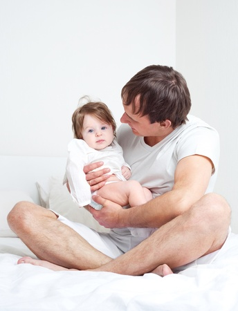 young father with his six months old daughter on the bed at home   Stock Photo - 9343082