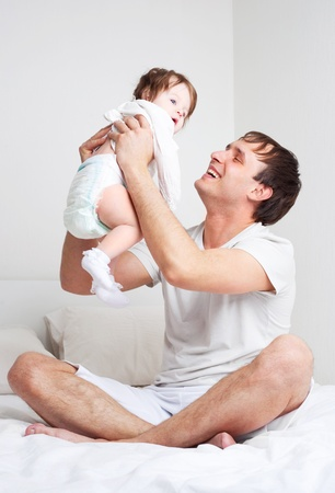 young father with his six months old daughter on the bed at home   Stock Photo - 9343085
