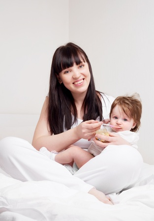 happy young mother feeding her baby with yogurt (focus on the mother) Stock Photo - 9343083