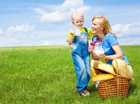 pouring milk: happy young  woman and her son having a picnic outdoor on a summer day