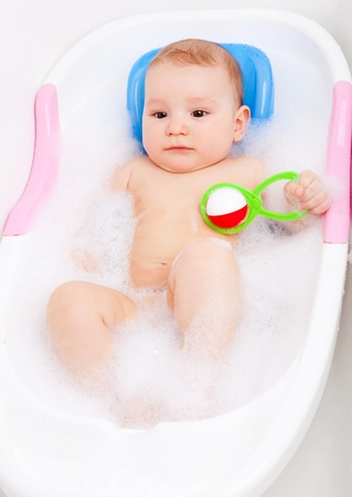 foam safe: cute six months old baby taking a bath with foam and playing with a toy