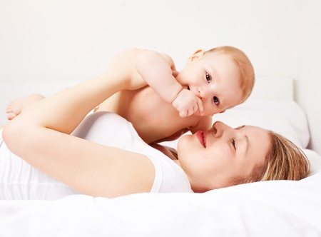 young  mother and her six months old baby on the bed at home photo