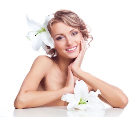 beautiful young blond woman sitting by the table with a lily in her hair photo