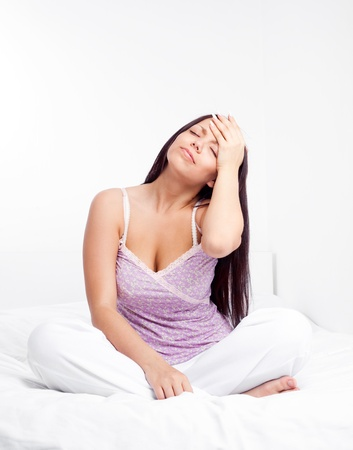 young woman having a headache, sitting on the bed at home Stock Photo - 9424867