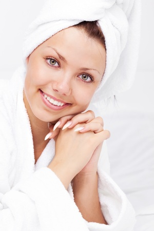 beautiful young woman wearing a towel and a white bathrobe on the bed at home Stock Photo