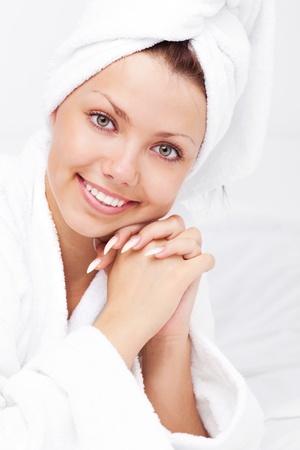 bathrobes: joven y bella mujer usando una toalla y una bata de ba�o blanco en la cama en su casa