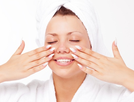beautiful young woman wearing a towel and a white bathrobe making herself face massage photo