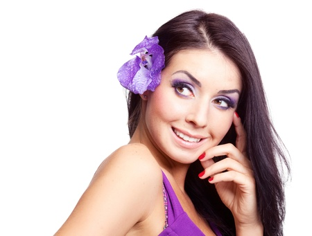 purple dress: beautiful happy  young brunette woman with  an orchid in her hair, looking to the left