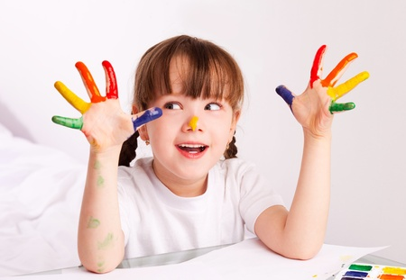 happy cute five year old girl sitting by the table and  painting with watercolor at home Stock Photo - 9480417