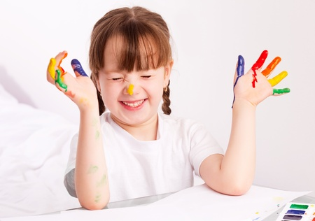 happy cute five year old girl sitting by the table and  painting with watercolor at home Stock Photo - 9480411