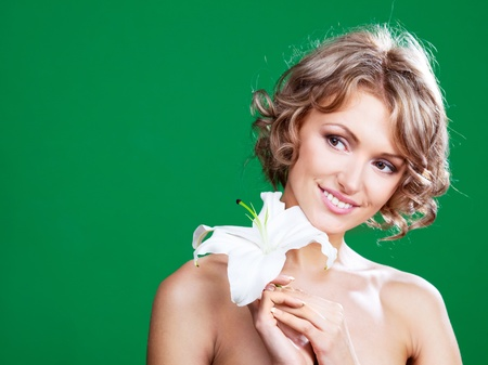 beautiful young blond woman  with a lily in her hair, against green background Stock Photo - 9480423