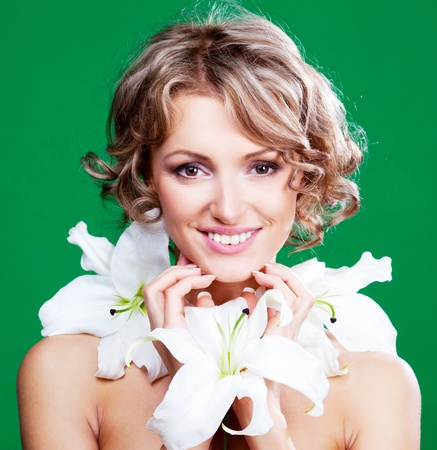 beautiful young blond woman  with a lily in her hair, against green background Stock Photo - 9480419