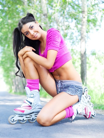 happy young brunette woman on roller skates in the park Stock Photo - 9480623