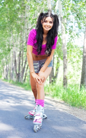 happy young brunette woman on roller skates in the park photo